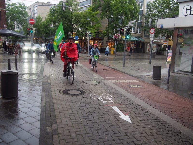 Radfahrende mit grüner Flagge mit Sonnenblumenlogo in der Neusser Innenstadt
